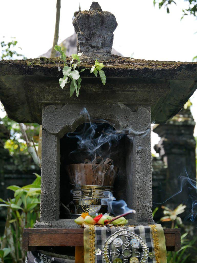 un petit temple avec une statue habillée et une offrande