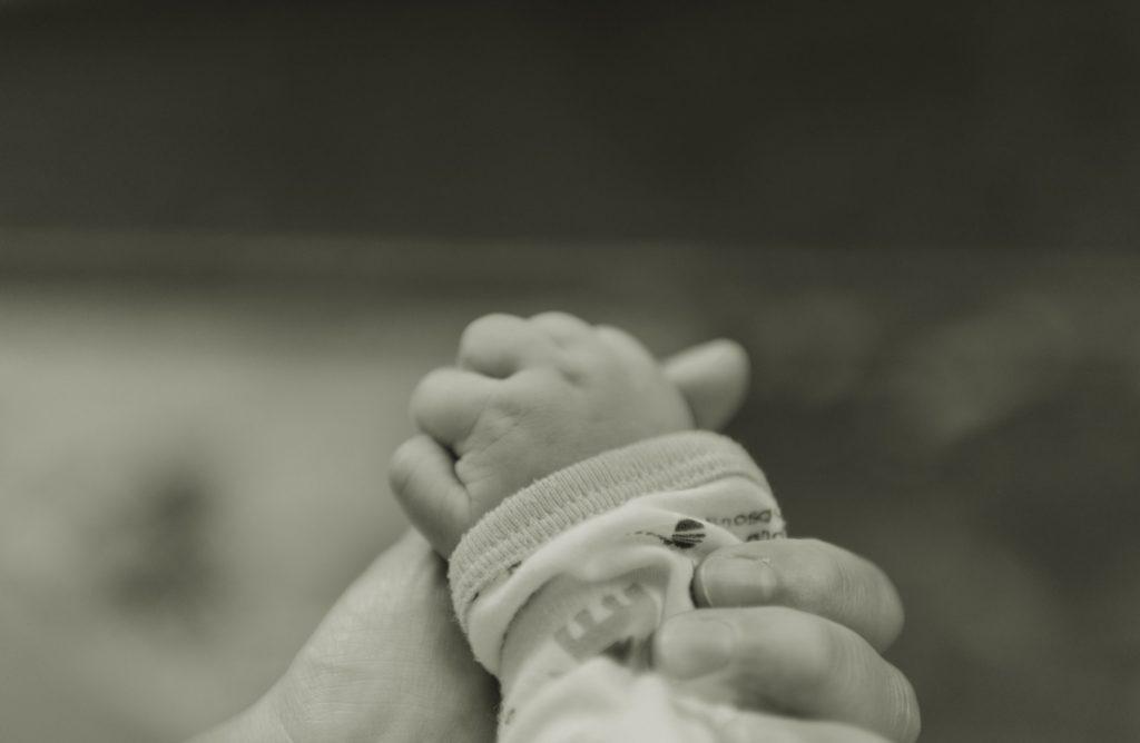 Une main d'un nouveau-né dans celle de son parent. Le toucher est indispensable.