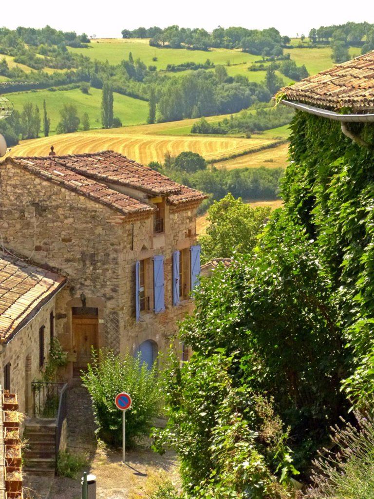 Un paysage d'été dans le sud de la France, avec des maisons en pierre et des champs de blé.
